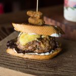 French onion soup stuffed burger on buttered French bread, melted mozzarella & swiss, herbes de Provence aioli, deep fried cornichon. Photo by Sean Neild
